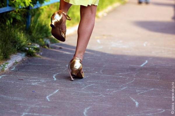 Милана прыгает в новеньких туфельках по клеточкам классиков.
