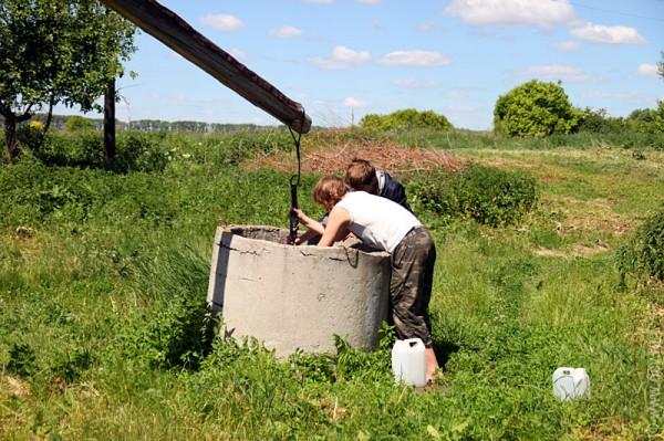 Парни добывают воду из колодца.
